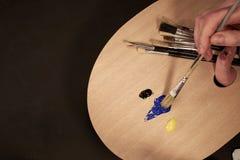 Βούρτσα εκμετάλλευσης χεριών με την παλέτα και πολλές βούρτσες Στοκ φωτογραφία με δικαίωμα ελεύθερης χρήσης