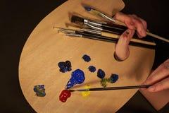 Βούρτσα εκμετάλλευσης χεριών με την παλέτα και πολλές βούρτσες Στοκ Εικόνες