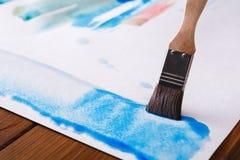 Βούρτσα στα χέρια Καλλιτέχνης που δημιουργεί τη ζωγραφική watercolor Στοκ Εικόνα