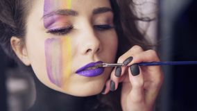 Βούρτσα χρήσεων καλλιτεχνών Makeup για να εφαρμόσει το κραγιόν για να διαμορφώσει τα χείλια ` s Πρότυπο με τα ψεύτικα μαστίγια κα φιλμ μικρού μήκους