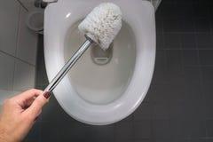 Βούρτσα χρήσης γυναικών για τον καθαρισμό του κύπελλου τουαλετών για την υγεία στοκ εικόνες