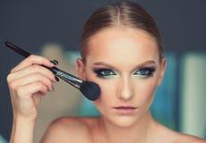 Βούρτσα χρήσης γυναικών για το makeup, visage Το πρότυπο ομορφιάς εφαρμόζει τη σκόνη στο πρόσωπο, καλλυντικά Γυναίκα με το νέο δέ στοκ εικόνα