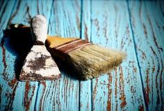 Βούρτσα χρωμάτων και ξύσιμο Trowel στο ξύλινο επιτραπέζιο χρώμα από το κυανό χρώμα Στοκ Φωτογραφία