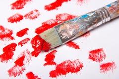 Βούρτσα χρωμάτων με τα κόκκινα κτυπήματα χρωμάτων πέρα από το λευκό Στοκ Φωτογραφίες