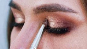Βούρτσα Makeup που εφαρμόζει τις σκιές ματιών στην όμορφη νέα κινηματογράφηση σε πρώτο πλάνο βλέφαρων γυναικών απόθεμα βίντεο