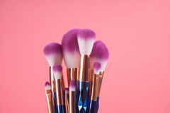 Βούρτσα Makeup που τίθεται στο κόκκινο ρόδινο υπόβαθρο κρητιδογραφιών Στοκ Φωτογραφία