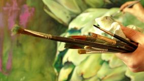 Βούρτσες εκμετάλλευσης ζωγράφων επαγγελματιών καλλιτεχνών στο χέρι της που σύρει ένα έργο τέχνης με τα ελαιοχρώματα απόθεμα βίντεο