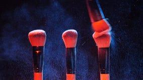 Βούρτσες καλλυντικών και ζωηρόχρωμη σκόνη makeup έκρηξης απόθεμα βίντεο