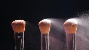 Βούρτσες καλλυντικών και ζωηρόχρωμη σκόνη makeup έκρηξης φιλμ μικρού μήκους
