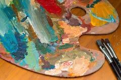 Βούρτσες παλετών και χρωμάτων σε έναν ξύλινο πίνακα Στοκ εικόνα με δικαίωμα ελεύθερης χρήσης