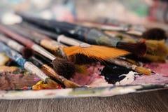 Βούρτσες χρωμάτων που τοποθετούνται στην παλέτα χρώματος, μακρο πυροβολισμός με το θολωμένο υπόβαθρο στοκ φωτογραφία με δικαίωμα ελεύθερης χρήσης