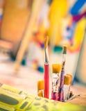Βούρτσες χρωμάτων σε ένα εκλεκτής ποιότητας ζωηρόχρωμο ατελιέ στοκ εικόνα