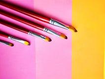 Βούρτσες χρωμάτων σε ένα υπόβαθρο του χρωματισμένου εγγράφου στοκ εικόνες