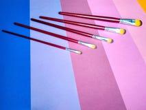 Βούρτσες χρωμάτων σε ένα υπόβαθρο του χρωματισμένου εγγράφου στοκ φωτογραφίες με δικαίωμα ελεύθερης χρήσης
