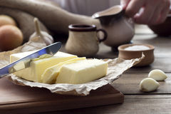 Βούτυρο με ένα μαχαίρι και ένα φλυτζάνι με το γάλα Στοκ Εικόνα