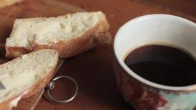 Βούτυρο σε ένα αγροτικό ψωμί κομματιού και φλιτζάνι του καφέ σε έναν ξύλινο παλαιό πίνακα Πρόγευμα απόθεμα βίντεο