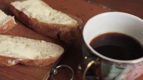 Βούτυρο σε ένα αγροτικό ψωμί κομματιού και φλιτζάνι του καφέ σε έναν ξύλινο παλαιό πίνακα Πρόγευμα φιλμ μικρού μήκους