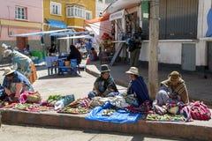Βολιβιανοί πλανόδιοι πωλητές που φορούν τα παραδοσιακά ενδύματα και τα καπέλα σφαιριστών στοκ εικόνα