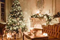 Βράδυ Χριστουγέννων από το φως ιστιοφόρου κλασικά διαμερίσματα με μια άσπρη εστία, διακοσμημένο δέντρο, καναπές, μεγάλα παράθυρα  Στοκ Φωτογραφίες