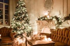 Βράδυ Χριστουγέννων από το φως ιστιοφόρου κλασικά διαμερίσματα με μια άσπρη εστία, διακοσμημένο δέντρο, καναπές, μεγάλα παράθυρα  Στοκ φωτογραφία με δικαίωμα ελεύθερης χρήσης