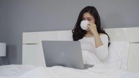 Βράση που πυροβολείται της γυναίκας που πίνει ένα φλιτζάνι του καφέ και που χρησιμοποιεί το φορητό προσωπικό υπολογιστή στο κρεβά απόθεμα βίντεο