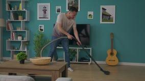 Βράση του καθαρίζοντας σπιτιού νεαρών άνδρων με την ηλεκτρική σκούπα απόθεμα βίντεο