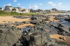 Βράχοι άμμου παραλιών ενάντια στον ορίζοντα πόλεων μπλε ουρανού Στοκ εικόνες με δικαίωμα ελεύθερης χρήσης