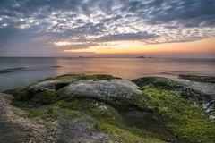 Βράχοι με τα φύκια ενάντια σε έναν ζωηρόχρωμο ουρανό, στοκ φωτογραφία με δικαίωμα ελεύθερης χρήσης