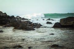 Βράχοι σε έναν ωκεάνιο κόλπο με τα κύματα στο υπόβαθρο Στοκ Φωτογραφίες