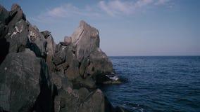 Βράχοι σε μια ακτή μια ηλιόλουστη ημέρα απόθεμα βίντεο