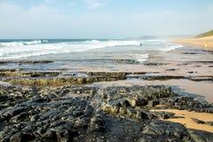 Βράχοι στην ακροθαλασσιά ενάντια στον ωκεάνιο και μπλε ορίζοντα Στοκ Εικόνες