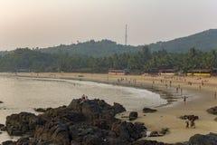 Βράχοι στη θάλασσα κοντά στην αμμώδη παραλία με τους ανθρώπους που στηρίζονται και που κολυμπούν στο υπόβαθρο στοκ εικόνα με δικαίωμα ελεύθερης χρήσης