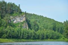 Βράχος απότομων βράχων στην ακτή του ποταμού με τα δασικά δέντρα το καλοκαίρι Στοκ Φωτογραφία