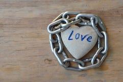 Βράχος καρδιών ρόλων αλυσίδων στον ξύλινο πίνακα στοκ φωτογραφία με δικαίωμα ελεύθερης χρήσης