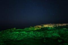 Βράχος νυχτερινός ουρανός έναστρος Θάλασσα Η θάλασσα έδωσε έμφαση στον πράσινο δείκτη λέιζερ Στοκ Φωτογραφία