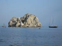 Βράχος σε μια θάλασσα και τους κόπτες Στοκ Εικόνες