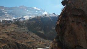 Βράχος στα βουνά ανώτερου Balkaria Η εναέρια άποψη του φαραγγιού με έναν βρώμικο δρόμο και ένα βουνό λικνίζει στα βουνά φιλμ μικρού μήκους
