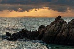 Βράχος στην ακτή στο πρώτο πλάνο κατά τη διάρκεια του ηλιοβασιλέματος με τη σειρά βουνών στο πορτοκαλί φως του ήλιου ως υπόβαθρο στοκ φωτογραφία με δικαίωμα ελεύθερης χρήσης