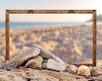 Βράχος στην παραλία με το κενό πλαίσιο εικόνων και τη θολωμένη παραλία και Στοκ Φωτογραφίες