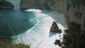 Βράχος στον ωκεανό με τους όμορφους φοίνικες πίσω στην παραλία Atuh στο νησί Nusa Penida, Ινδονησία απόθεμα βίντεο