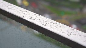 Βρέχοντας πτώση στη ράγα μπαλκονιών ανοξείδωτου στη βροχερή ημέρα, σταγονίδια βροχής στο πεζούλι απόθεμα βίντεο