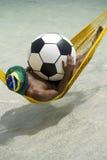 Βραζιλιάνα χαλάρωση με το ποδόσφαιρο ποδοσφαίρου στην αιώρα παραλιών Στοκ εικόνα με δικαίωμα ελεύθερης χρήσης