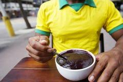 Βραζιλιάνο άτομο που τρώει το κύπελλο Acai Açaí στοκ εικόνες