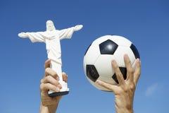 Βραζιλιάνο ποδόσφαιρο σφαιρών ποδοσφαίρου εκμετάλλευσης χεριών και άγαλμα Χριστού Corcovado Στοκ φωτογραφίες με δικαίωμα ελεύθερης χρήσης