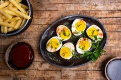 Βρασμένα αυγά και γαλλικές πυρκαγιές σε έναν πίνακα στοκ εικόνες
