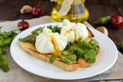 Βρασμένα αυγά σε μια σακούλα & x28 poached& x29  στην τριζάτη φρυγανιά και τα πράσινα φύλλα arugula στοκ φωτογραφία