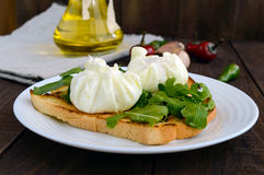 Βρασμένα αυγά σε μια σακούλα & x28 poached& x29  στην τριζάτη φρυγανιά και τα πράσινα φύλλα arugula στοκ φωτογραφίες