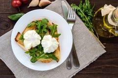 Βρασμένα αυγά σε μια σακούλα & x28 poached& x29  στην τριζάτη φρυγανιά και τα πράσινα φύλλα arugula στοκ φωτογραφία με δικαίωμα ελεύθερης χρήσης