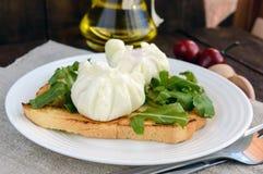 Βρασμένα αυγά σε μια σακούλα & x28 poached& x29  στην τριζάτη φρυγανιά και τα πράσινα φύλλα arugula στοκ εικόνα