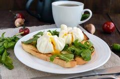 Βρασμένα αυγά σε μια σακούλα & x28 poached& x29  στη φρυγανιά και τα τραγανά πράσινα φύλλα του arugula και ενός φλυτζανιού του τσ στοκ φωτογραφίες με δικαίωμα ελεύθερης χρήσης